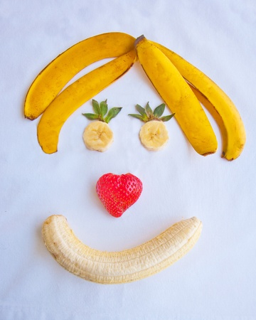 Smiling face made from bananas and strawberries