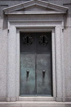 Classical metal door to a tomb surrounded by a stone facade