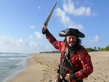 attacking: Threatening Pirate. A menacing, black bearded pirate raises his sword as he runs on the beach Stock Photo