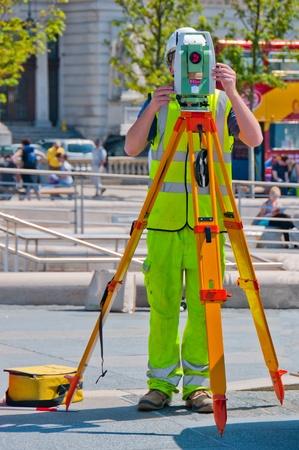 Surveyor.A construction surveyor working in a busy street