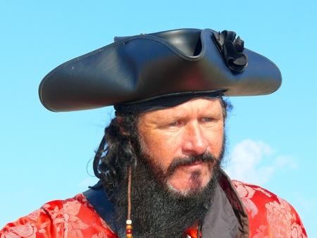 Head and shoulders portrait of a black bearded pirate wearinga tricornered hat.