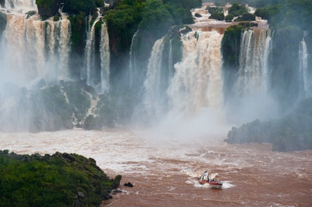 Iguazzu Falls. A boat full of tourists enjoy a close-up view of the falls , bordering Argentina and Brazil Stock Photo