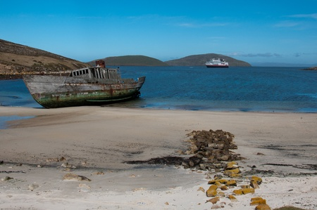 Shipwreck on Antarctic Beach. A derelict boat washed ashore with modern cruiseship in background