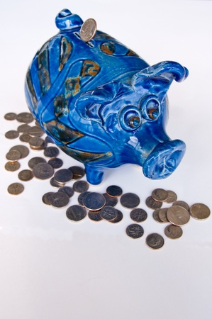 thrifty: Blue piggy bank with coins on white background.