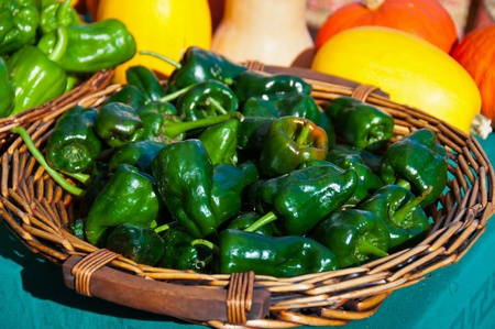 A wicker basket with green peppers and squash in the background.