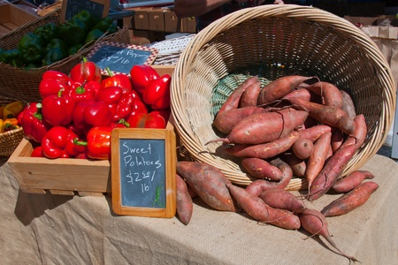 A basket of sweet potatoes with red peppers  at a local farmers market.