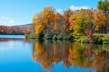 autumn colour: Colorful autumn foliage casts its reflection on the calm waters of the North Carolina lake.
