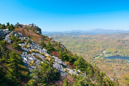 Tourists climb to the mountaintop overlooking the North Carolina fall scenery.