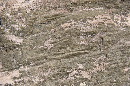 Surface of a rock showing lines and sand.