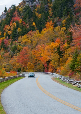 A car  travels the scenic Blue Ridge surrounded by colorful fall foliage.