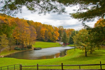 Lake house with Fall foliage, N C   Scenic autumn view of North Carolina home framed with tree branches and country fence