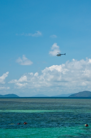 A helicopter flies over snorkelers at Green Island, near Cairns. Stock Photo