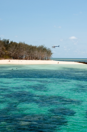 A helicopter lands on the beach at Green Island, near Cairns Stock Photo - 18703969