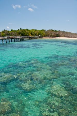 barrier island: Visitors to Green Island, near Cairns, cross the pier to board their boats