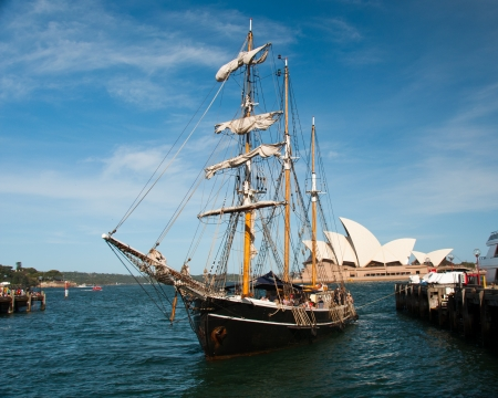 A tall masted ship anchors in Sydney Harbor.