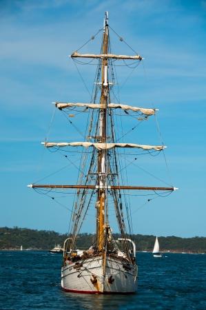 A tall ship makes its way across Sydney Harbor