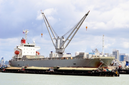 Vessel bulk cargo with crane and lighter in the river Editorial
