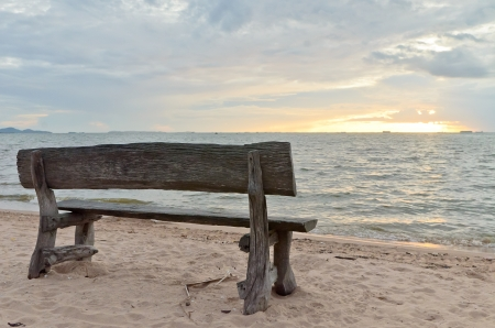Wooden bench on the beach with sunset photo