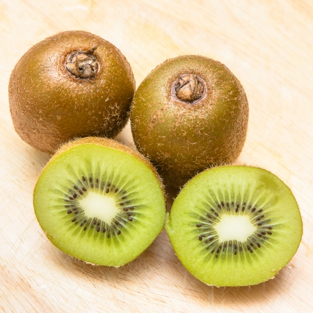 Whole kiwi fruit and his sliced segments on chopping block photo