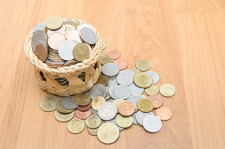 Thai baht coins in basket on wooden floor Stock Photo - 24064737