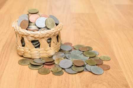 Thai baht coins in basket on wooden floor photo
