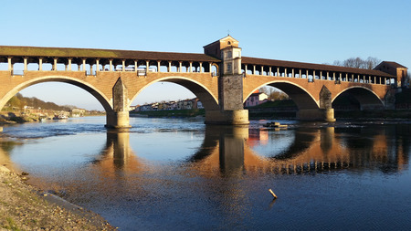 miror: Covered bridge over water mirror. Pavia, Italy.