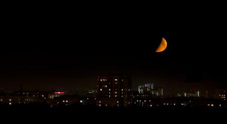 stimulus: big bloody moon near the horizon in the city Stock Photo
