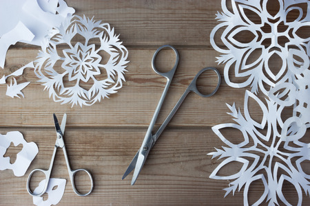 handmade paper snowflakes and scissors on table