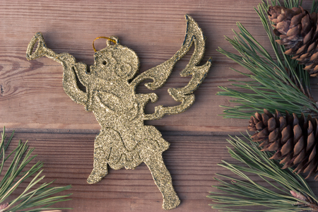 cherub: golden Christmas cherub and Christmas tree branches on wooden table