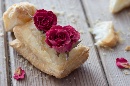 puff: tasty cookies with dry roses on wooden table Stock Photo