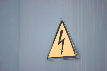 powerlines: triangle yellow electricity sign on grey background