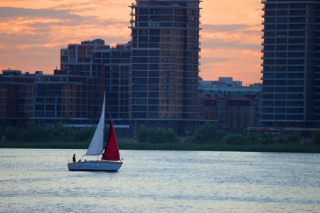 sailing boat with red sail in the city Editorial