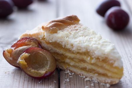 Pastel de dulce con ciruela en la mesa de madera
