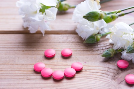 Birth control pink pills and white flower Archivio Fotografico