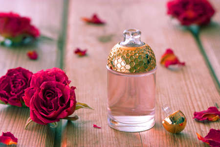 bath supplement: perfume bottle and pink roses on wooden table