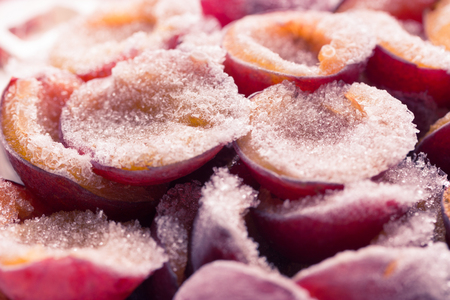 frozen half of a plum on a wooden background. Winter vitamins