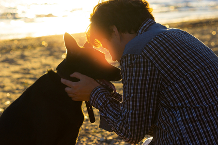 true bred: man and his dog on the beach. best friends Stock Photo