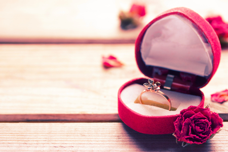 Golden engagement ring in a heart shaped box and roses