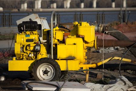 Mashine de evacuación de agua amarilla sobre fondo de construcción Foto de archivo