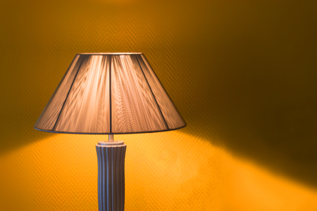 Nice luminous desk lamp on ginger background with copy space