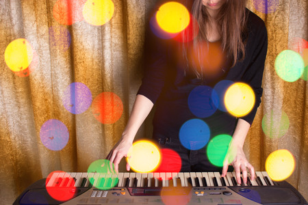 unrecognizible girl musician playing on electronic piano. dolden background Stock Photo
