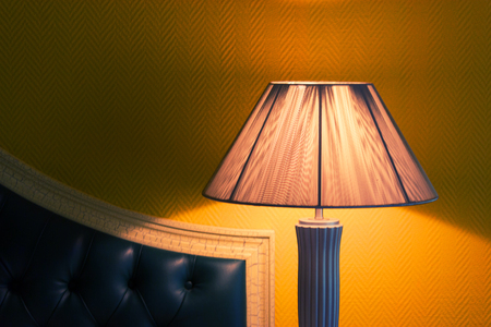 Desk Lamp with Bed. yellow wallpaper background Stock Photo