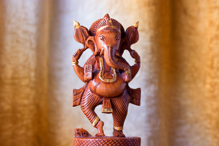 indian godness ganesha wooden figurine. golden background
