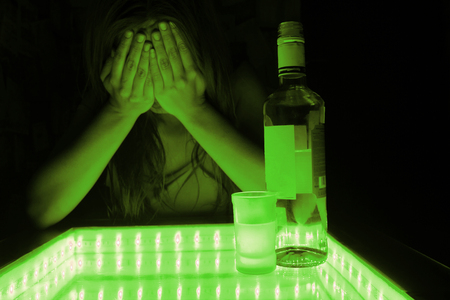 dreaminess: young woman cry. alcohol beside her. depression, problems concept