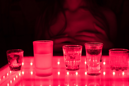 young prostitute in a club with alcohol drinks