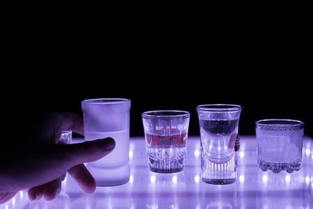 many shot on illuminated table. hand grab one shot Stock Photo