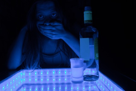 alcohol intoxication concept. woman in a bar feel sick because of alcohol Stock Photo