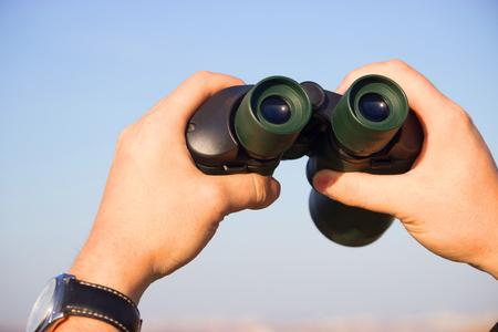 binocular in mans hands on the blue sky background