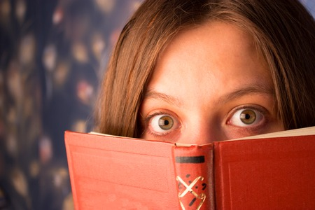 scared girl with a book, reading horrors