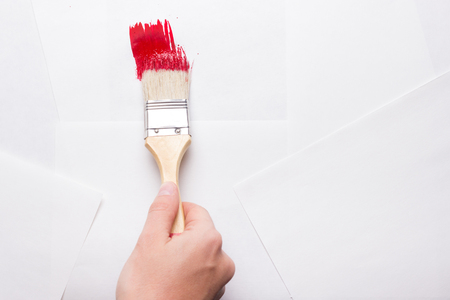 paintcan: construction brush in hand on white background. not isolated. copy space